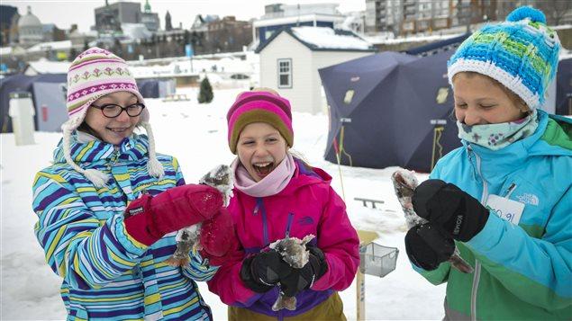 De jeunes filles s'amusent avec les truites qu'elles ont attrapées.  Photo :  Radio-Canada/Marie-Eve Maheu