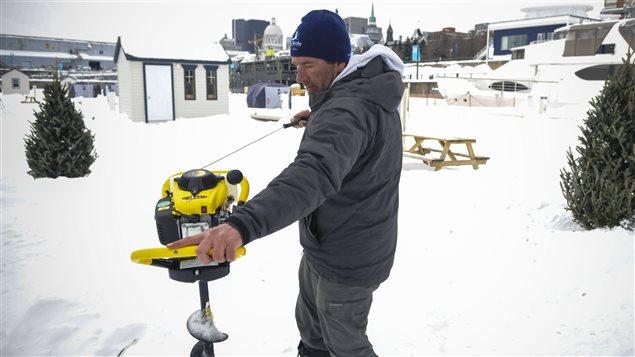 Jean Desjardins, propriétaire de Pêche sur glace Vieux-Montréal, creuse un trou pour la pêche.  Photo :  Radio-Canada/Marie-Eve Maheu